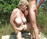 Busty granny fucked outdoors with younger man